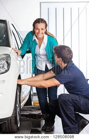 Happy Customer Standing By Mechanic Changing Tire