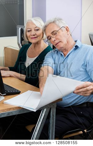 Senior Man Showing Notes To Classmate During Computer Class