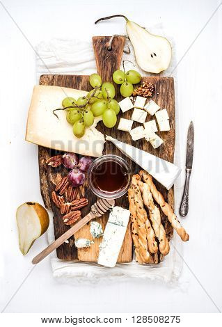 Cheese appetizer set. Various types of cheese, honey, grapes, pear, nuts and bread grissini sticks on rustic wooden board over white background, top view