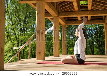Young girl is engaged in yoga on the wooden terrace on the nature background. She sits sideways in the lotus pose on the red yoga mat and stretches her connected hands over the head. She wears black shorts and white cardigan.