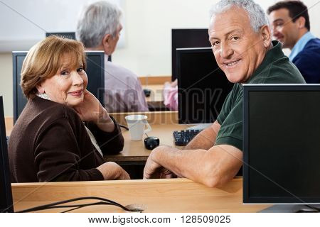 Happy Senior Students Sitting At Desk In Computer Class