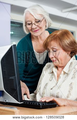 Woman Assisting Female Friend In Using Computer At Classroom