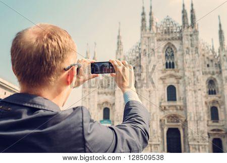 Traveler take a photo of Duomo di Milano with his smartphone