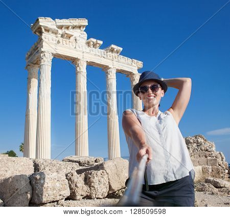 Pretty young woman take a self photo on the antique temple view. Temple of ApolloSideTurkey