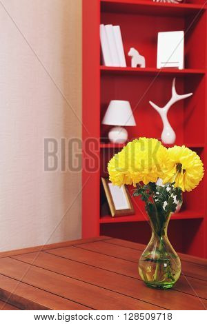 Modern interior design. Living room with bookcase and table with flowers