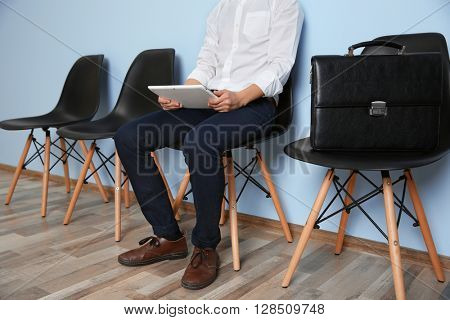 Young man in suit sitting on chair with tablet and waiting for job interview indoors