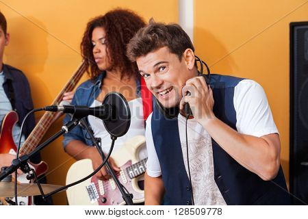 Happy Male Singer Wearing Headphones While Performing With Band