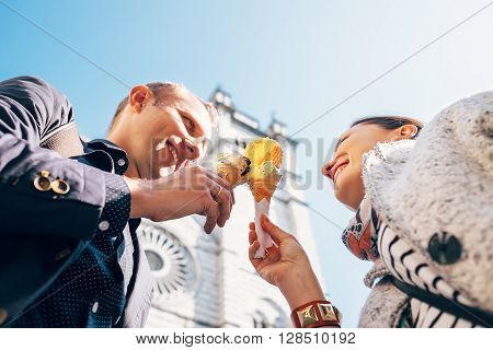 Couple in love with ice-cream cones on San Lorenco Cathedral background in Genova