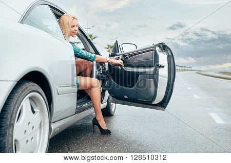 Beautiful young lady came out frome her car on the road