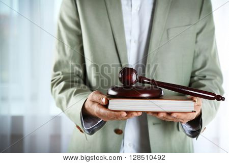 Man holding book with wooden gavel closeup
