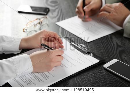 Human hands with pens working with documents at the desk closeup