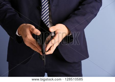 Man in a suit showing an empty purse on blue background