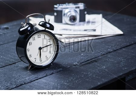 Alarm Clock With Camera And Newspaper On Table