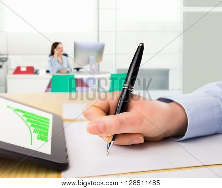 closeup of a businesswoman working with tablet and analyzing chart on the desk at the office with coworkers at the bacground