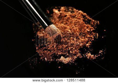 Make up brush and brown eye shadow on dark background