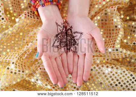 Henna tattoo on female hands, top view