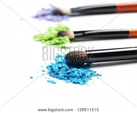 Makeup brushes with cosmetic powder isolated on white
