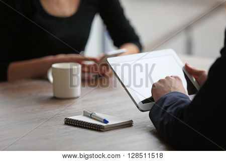 Business partners working with tablet and mobile phone at the table
