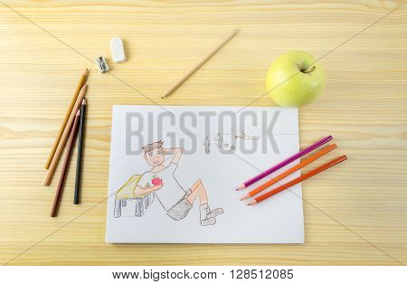 desk with drawing of a child eating apple that played football with apple and pencils on a wooden table