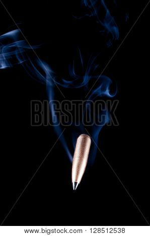 Copper plated bullet with a polymer tip approaching the viewer