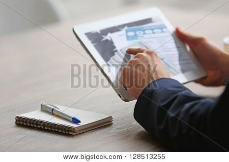 Man's hands using tablet at the table