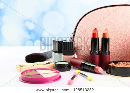 Makeup set with beautician, brushes and cosmetics on light background
