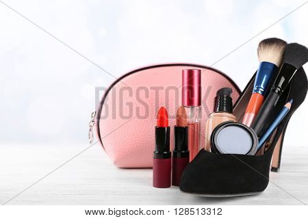 Makeup set with black woman's shoe, beautician, brushes and cosmetics on white background