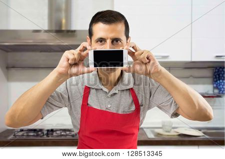 chef holding mobile phone over his mouth at the kitchen