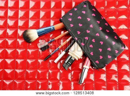 Makeup set with beautician, brushes and cosmetics on red background
