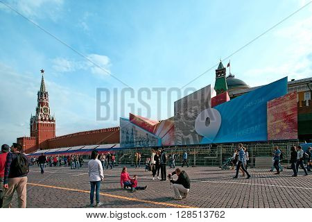 MOSCOW RUSSIA - MAY 02: Victory Day decoration on the Red Square. Spasskaya Tower at left people walkingKremlin wall a banner with May 9 at right . Taken on May 2 2016 in Moscow Russia.