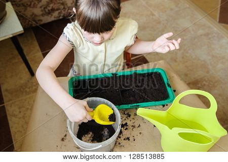 Beautiful girl in a yellow dress is gaining ground with a shovel from a bucket