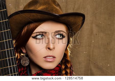portrait of a beautiful young red-haired girl in a country-style guitar fretboard