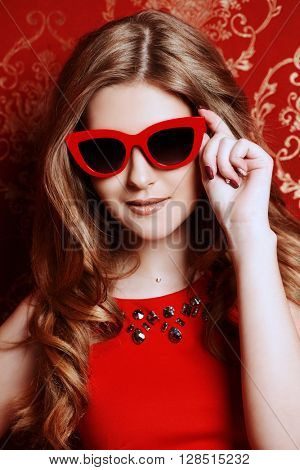 Portrait of a pretty woman in red dress and sunglasses in pin-up style. Fashion shot.
