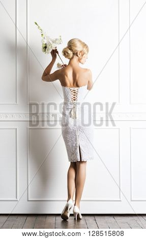 Young and beautiful bride in white dress posing in retro interior