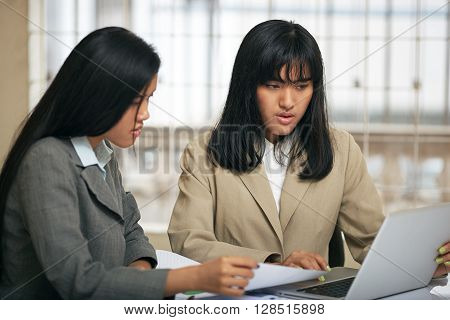 close up image of businesswomen discussing and consulting document