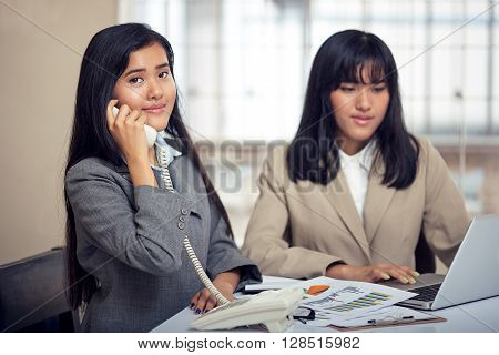 two friendly businesswomen discussing and consulting document