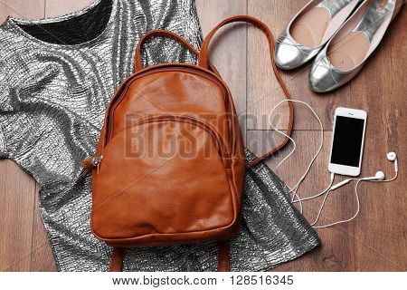 Brown leather backpack with female items on wooden surface, top view