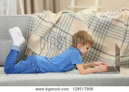 Little boy using laptop on sofa indoors