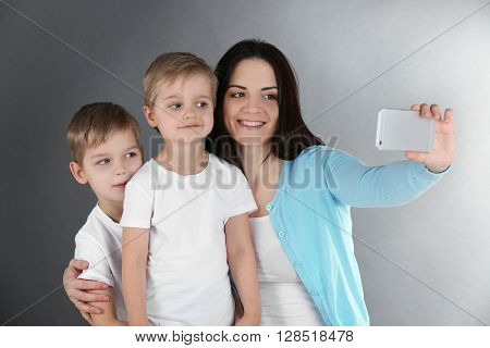 Smiling mom making selfie with her sons on grey background