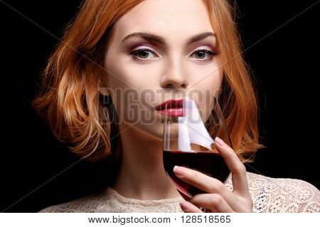 Young woman with glass of red wine on black background