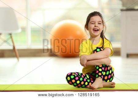 Little funny girl sitting on a mat indoor