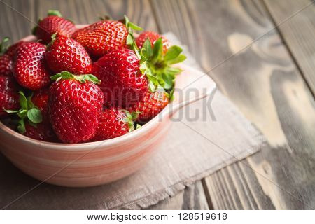 Fresh ripe strawberries in a pink bowl and linen napkin on wooden table.