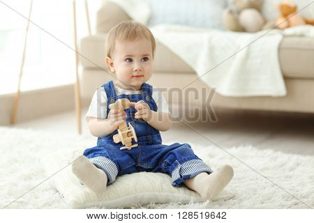 Baby playing with a toy helicopter on the floor