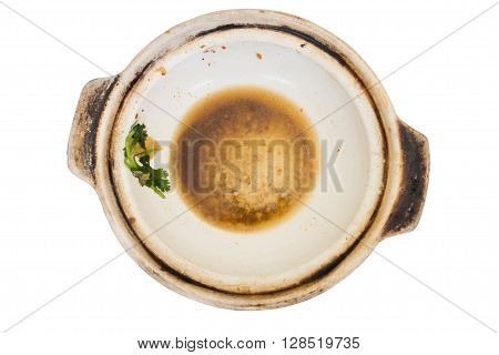 Empty white clay pot dirty with greasy and some vegetables after meal isolated on white background. Clay pot can be versatile.;