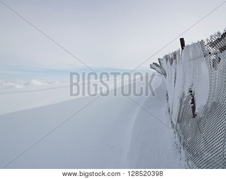 Old netting fence covered with snow on the endless snowbound field