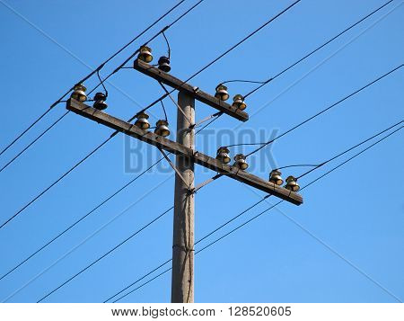 Electricity power pole with cable lines and insulators against the cloudless blue sky