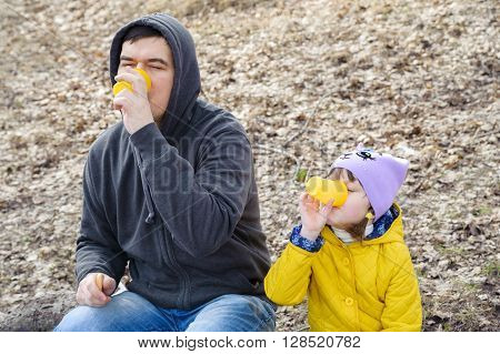Man and girl sitting on a log and drink from yellow plastic cups in nature