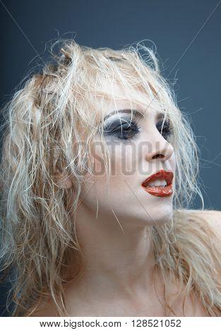 Blond female witch with strange makeup. Studio photo
