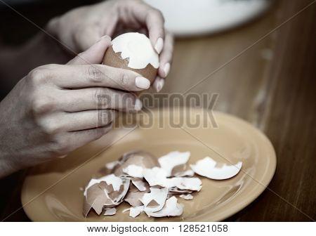 Closeup photo of the Human hands preparing boiled egg