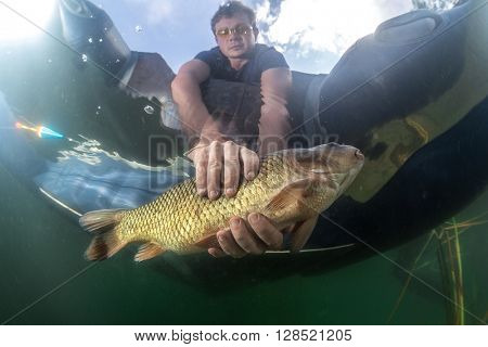 The underwater scenes. A fisherman in a boat holding a fish in the water